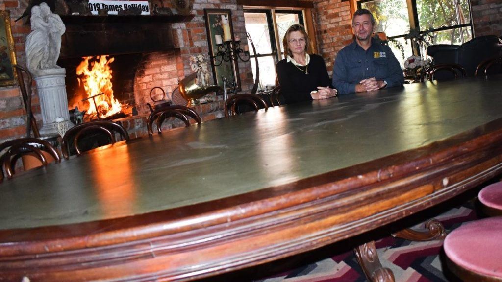 Robert and Therese Fenwick sit around what they claim to be 'Queensland's oldest relic', a table used by politicians from 1860 onward. Picture: Matthew Purcell