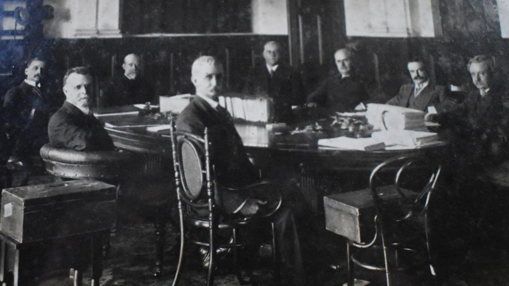 Queensland political dignitaries, including the Premier and Governor, sit around the table in 1914.
